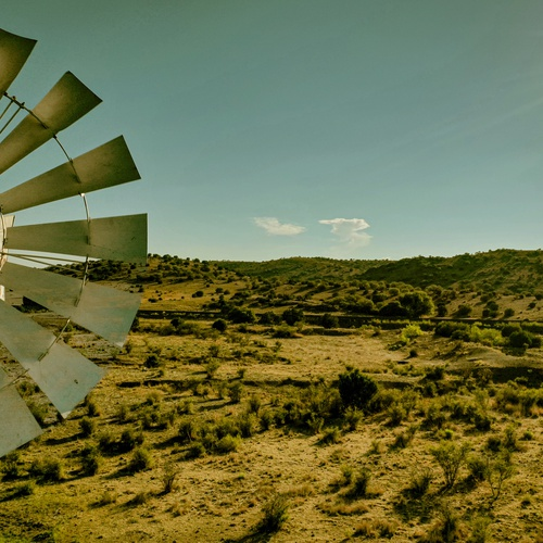 A lonely windmill stands tall in the desert