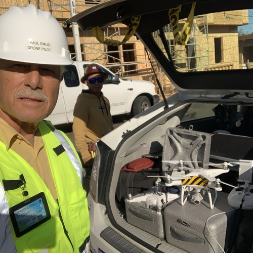 Hard hat, vest, and two Phantom 4 Pros